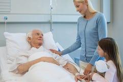 Familia que visita al abuelo enfermo imagen de archivo