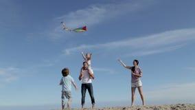 Familia que vuela una cometa en la playa almacen de video