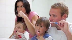 Familia reflejada en dientes de cepillado del espejo del cuarto de baño metrajes