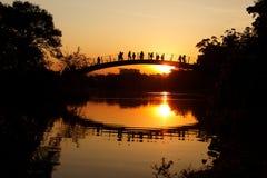 Familia romántica de la puesta del sol en el puente Imagenes de archivo