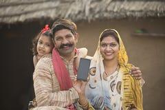 Familia rural encantada que sostiene el nuevo teléfono móvil imagen de archivo libre de regalías