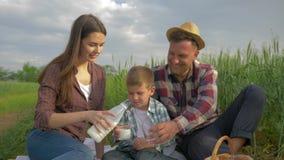 Familia rural, leche de colada de la mujer feliz en el vidrio al hijo y marido durante comida campestre en naturaleza en campo de metrajes