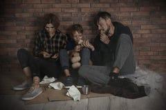 Familia sin hogar pobre que se sienta en piso cerca de la pared imágenes de archivo libres de regalías