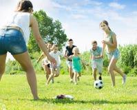 Familia sonriente con cuatro niños que corren después de bola Imágenes de archivo libres de regalías