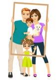 Familia sonriente con el hijo, la hija y el perro mirando a través de un marco vacío Fotos de archivo