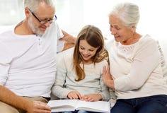 Familia sonriente con el libro en casa Foto de archivo libre de regalías