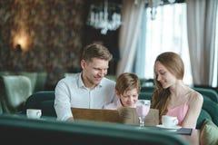 Familia sonriente con el menú Imágenes de archivo libres de regalías