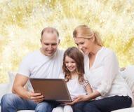 Familia sonriente con el ordenador portátil Fotos de archivo