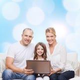 Familia sonriente con el ordenador portátil Fotos de archivo libres de regalías