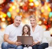 Familia sonriente con el ordenador portátil Imagen de archivo