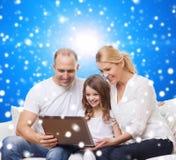 Familia sonriente con el ordenador portátil Imagen de archivo libre de regalías