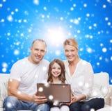 Familia sonriente con el ordenador portátil Fotografía de archivo