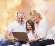 Familia sonriente con el ordenador portátil Foto de archivo libre de regalías