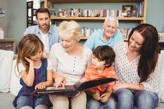 Familia sonriente con los abuelos con el álbum de foto Imágenes de archivo libres de regalías