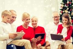 Familia sonriente con los ordenadores de la PC de la tableta en casa foto de archivo