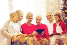 Familia sonriente con los ordenadores de la PC de la tableta en casa imágenes de archivo libres de regalías