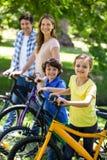 Familia sonriente con sus bicis Imágenes de archivo libres de regalías