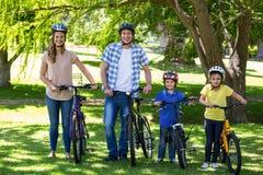 Familia sonriente con sus bicis Foto de archivo libre de regalías