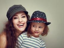 Familia sonriente de la moda en casquillos. Gir de risa de la madre y del niño de la diversión Imagenes de archivo