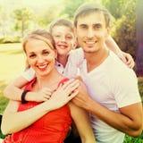 Familia sonriente de tres en prado verde Foto de archivo libre de regalías