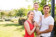 Familia sonriente de tres en prado verde Imagenes de archivo