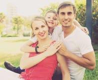 Familia sonriente de tres en prado verde Fotos de archivo libres de regalías