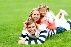 Familia sonriente de tres llenada encima de uno a fotos de archivo