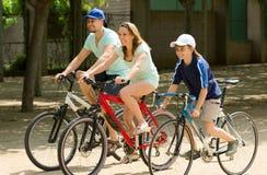 Familia sonriente de tres que completan un ciclo en el camino Fotos de archivo