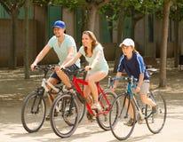 Familia sonriente de tres que completan un ciclo en el camino de la calle Imagenes de archivo