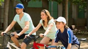 Familia sonriente de tres que completan un ciclo en la calle de la ciudad Foto de archivo libre de regalías