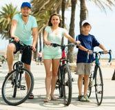 Familia sonriente de tres que completan un ciclo a través de ciudad Fotos de archivo libres de regalías