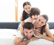 Familia sonriente en cama fotos de archivo libres de regalías