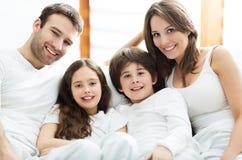 Familia sonriente en cama Imágenes de archivo libres de regalías