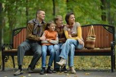 Familia sonriente en el bosque del otoño que se sienta en banco Foto de archivo libre de regalías
