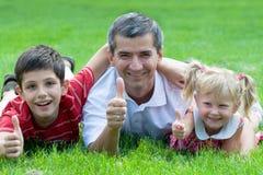 Familia sonriente en el parque Fotos de archivo libres de regalías