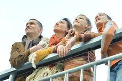 Familia sonriente en el parque que mira para arriba Foto de archivo libre de regalías