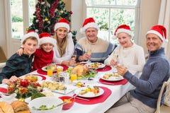 Familia sonriente en el sombrero de santa que tuesta a la cámara Imagen de archivo libre de regalías