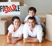 Familia sonriente en el suelo después de comprar la casa Imágenes de archivo libres de regalías