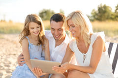 Familia sonriente en la playa con el ordenador de la PC de la tableta Fotos de archivo libres de regalías