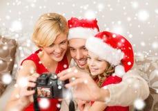 Familia sonriente en los sombreros del ayudante de santa que toman la imagen Foto de archivo