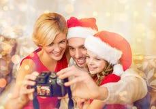 Familia sonriente en los sombreros del ayudante de santa que toman la imagen Fotos de archivo libres de regalías