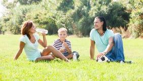 Familia sonriente en parque del verano Fotografía de archivo