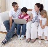 Familia sonriente en sala de estar usando una computadora portátil Fotografía de archivo libre de regalías
