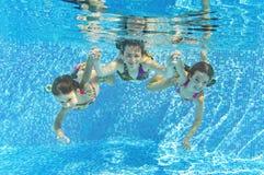 Familia sonriente feliz bajo el agua en piscina Fotografía de archivo