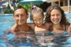 Familia sonriente feliz con la muchacha en el abrazo de la piscina fotos de archivo libres de regalías