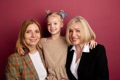 Familia sonriente feliz de Portraitof Ni?o con la mam? y la abuelita en un estudio fotografía de archivo libre de regalías