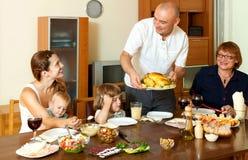 Familia sonriente feliz de tres generaciones que come el pollo con el vino Imagenes de archivo