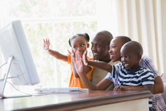 Familia sonriente feliz que charla con el ordenador junto Fotos de archivo libres de regalías