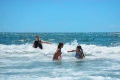 Familia sonriente feliz que se divierte en el océano hermoso Fotos de archivo libres de regalías