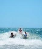 Familia sonriente feliz que se divierte en el océano hermoso Imagen de archivo